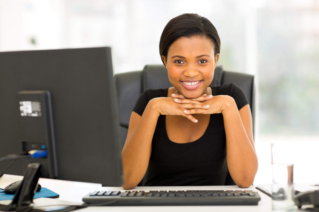 Get started with Career Start - Smiling woman in front of a computer.