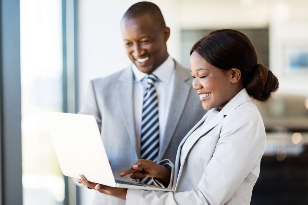 Direct Hire Staffing Services - A man in a suit looks at a laptop being held by a woman in a suit