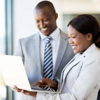 Executive Recruitment - A man in a suit looks at a laptop a woman in a suit is holding