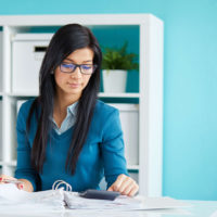 Payroll and Human Resource Services - A woman sits at a desk reviewing paperwork
