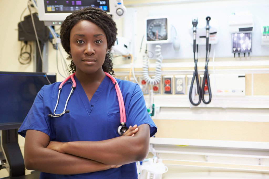 Direct Placement Staffing - A nurse in scrubs wearing a stethoscope around her neck, standing in front of medical equipment.
