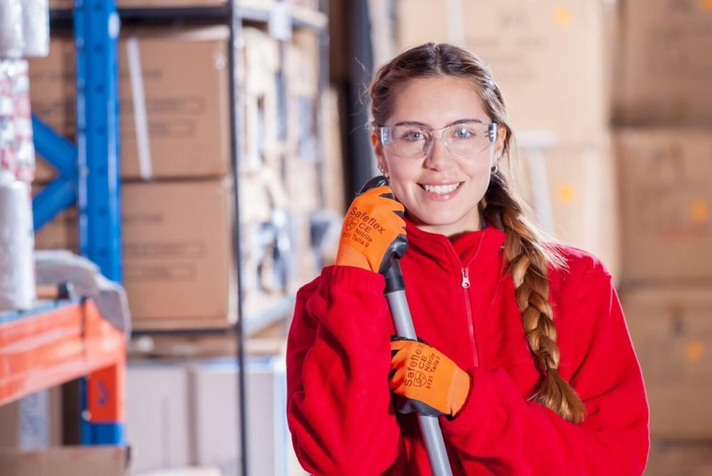 Temporary Staffing - A woman in a red sweatshirt and work goggles holds a broom in a warehouse