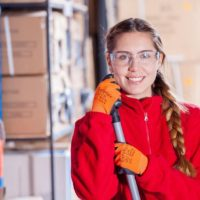 Recruitment for Temporary Staffing - Woman in a red sweatshirt and work goggles smiling and holding a broom