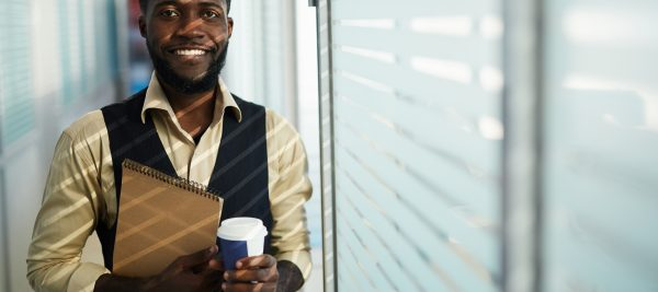 Male employee with folder and coffee.